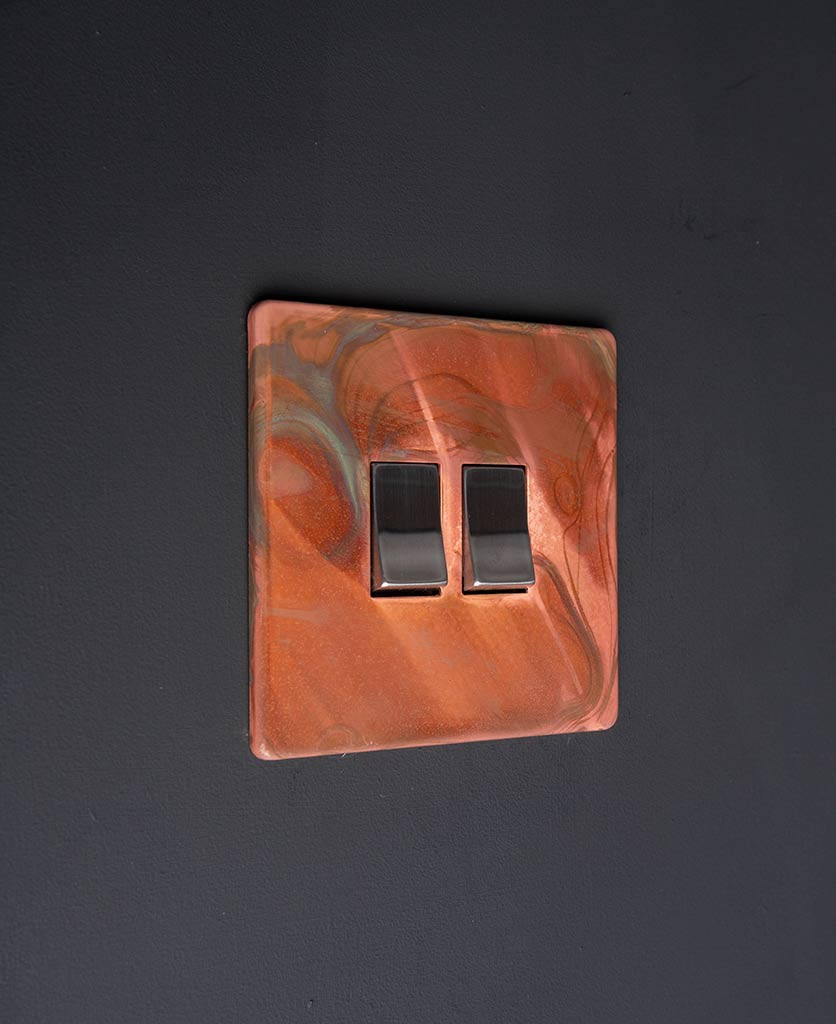 brushed copper light switch with double silver rocker detail on black wall