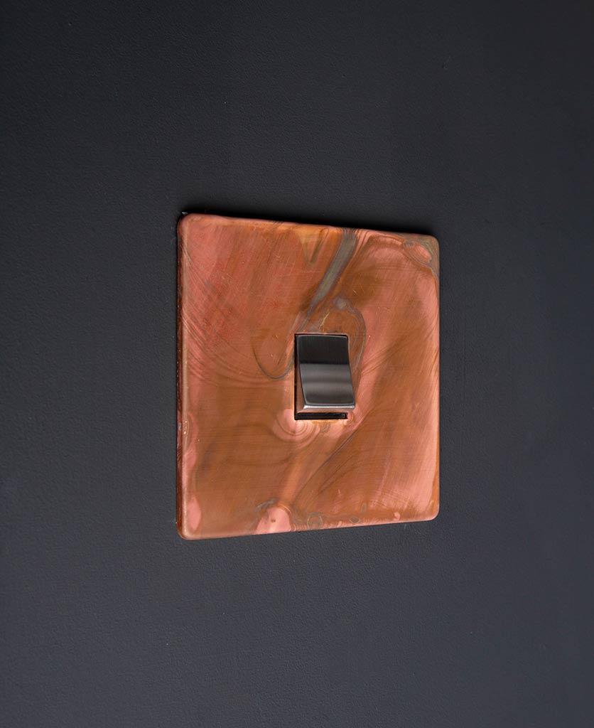 intermediate copper light switch with single silver rocker detail on black wall