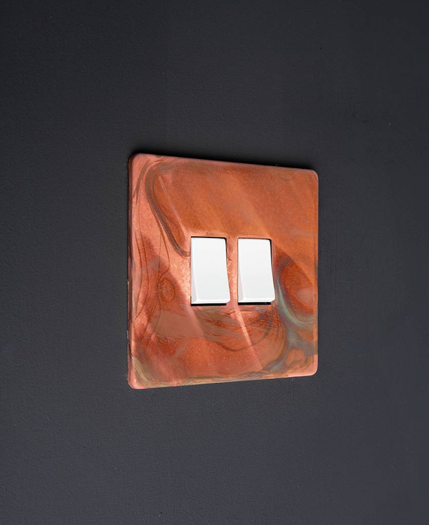 brushed copper light switch with double white rocker detail on black wall