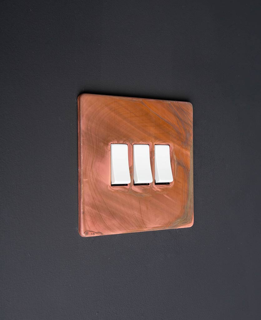 tarnished copper light switch with triple white rocker detail on a black wall