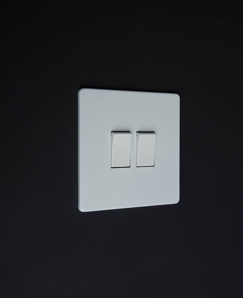 white double rocker switch with double white rocker detail on a black wall