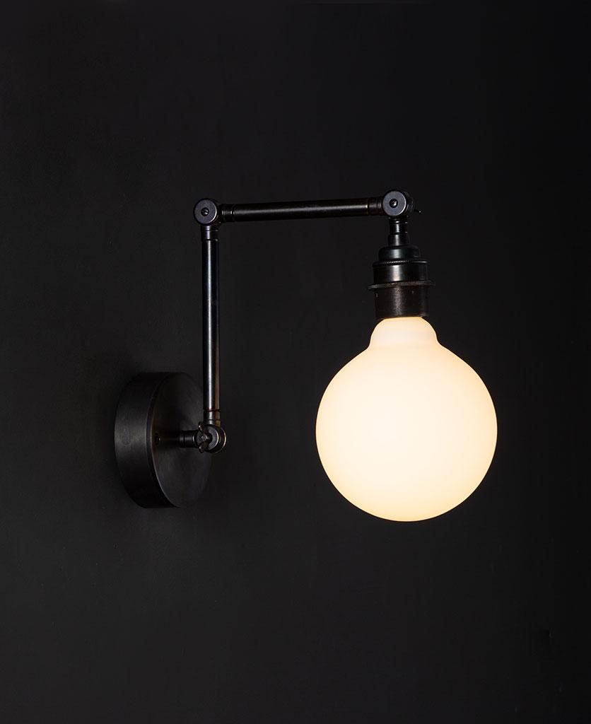 fender antique black wall light with lit opal bulb against black background