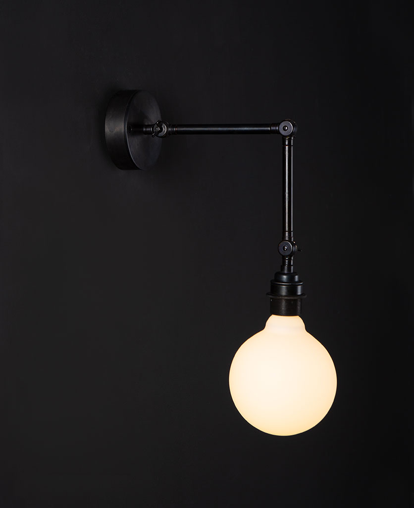 antique black wall light fender with lit opal bulb against black background