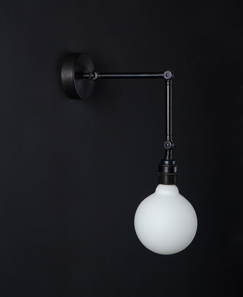 fender antique black wall light with unlit opal led bulb against black background