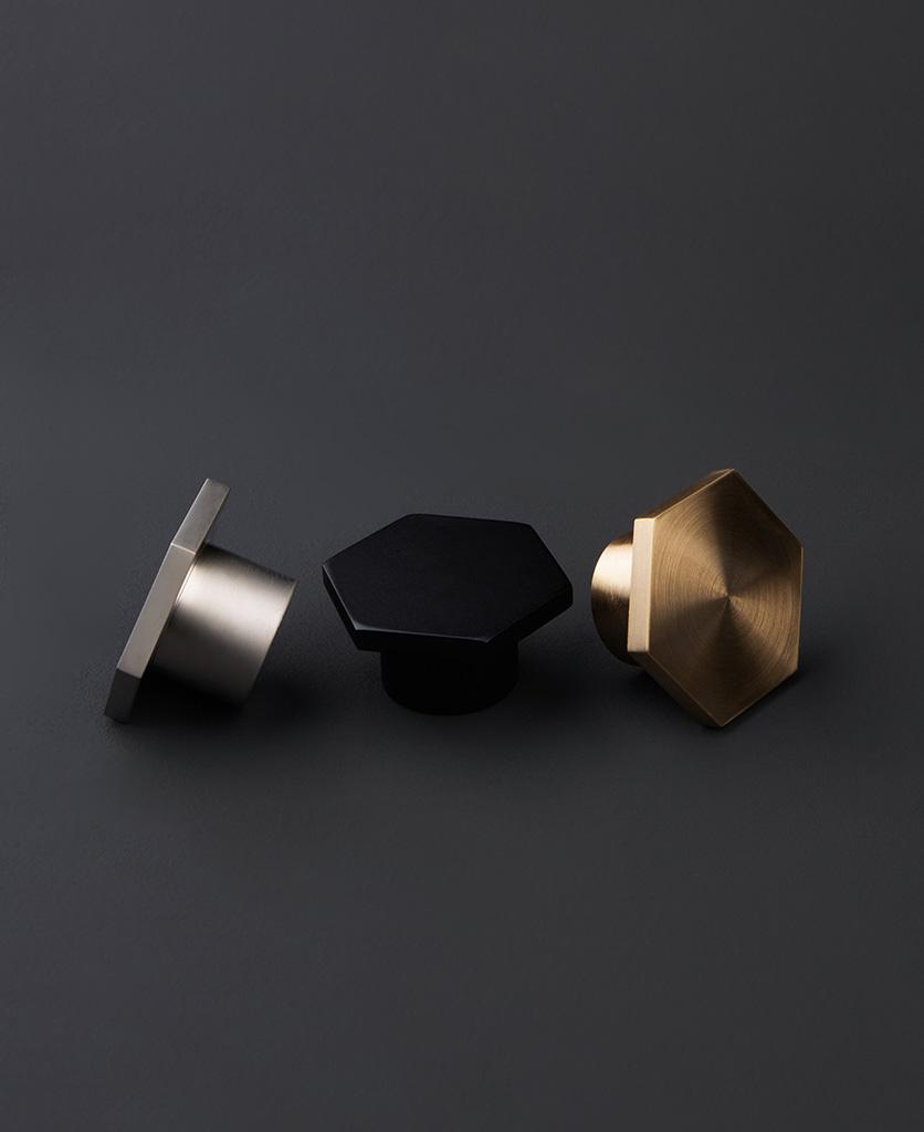 bauhaus hexagonal knob in black silver and gold against dark grey background