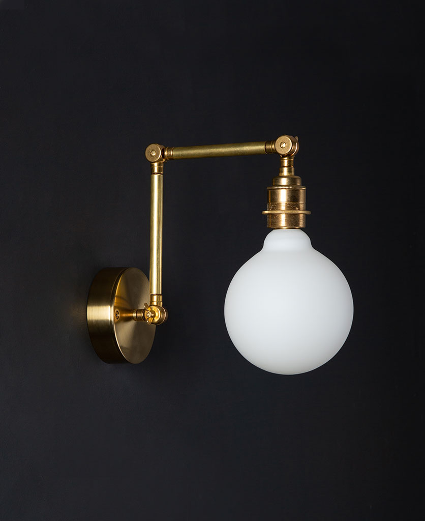 fender brass wall light with unlit opal bulb against black background