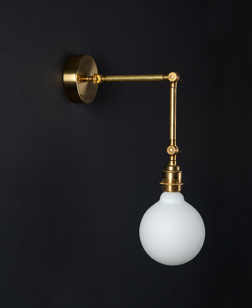 brass wall light fender with unlit opal bulb against black background
