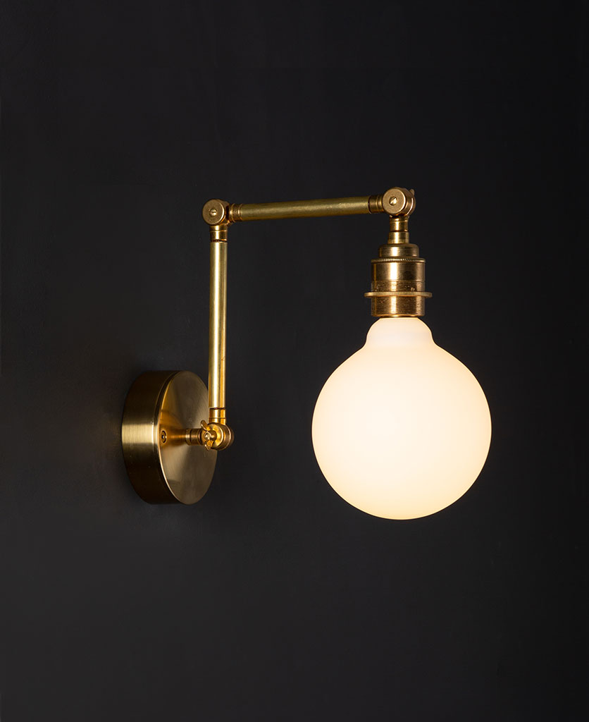 fender brass wall lights with lit opal bulb against black background