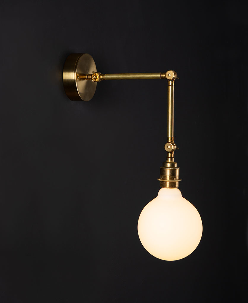 brass wall light fender with lit opal bulb against black background
