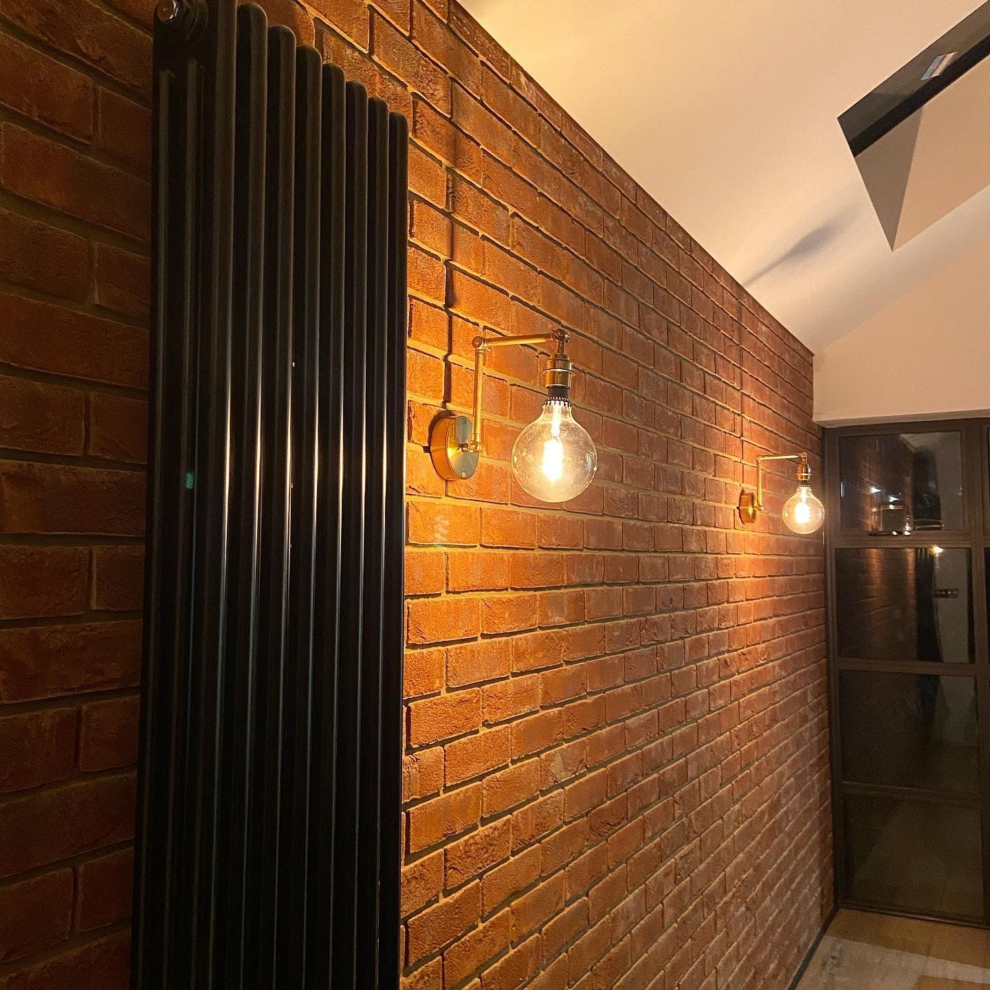 two brass fender wall lights fixed upon a brick wall