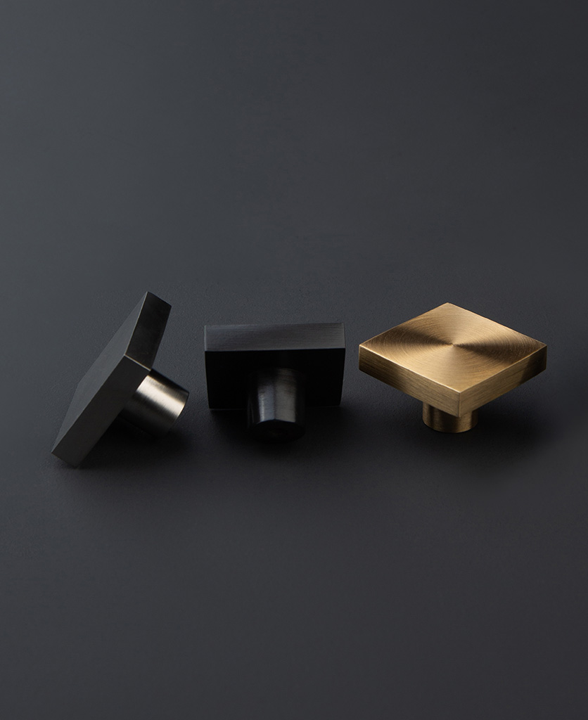 expressionist black gold and silver square wall coat hooks against dark grey background