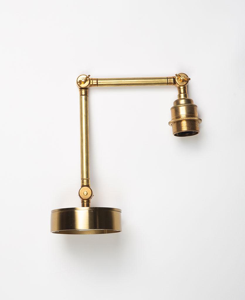 fender brass wall light on white background