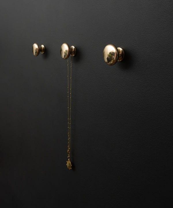 realist decorative wall hooks three gold wall hooks on a black wall