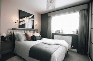 pink and dark green bedroom with white bedding and bramley wall lights