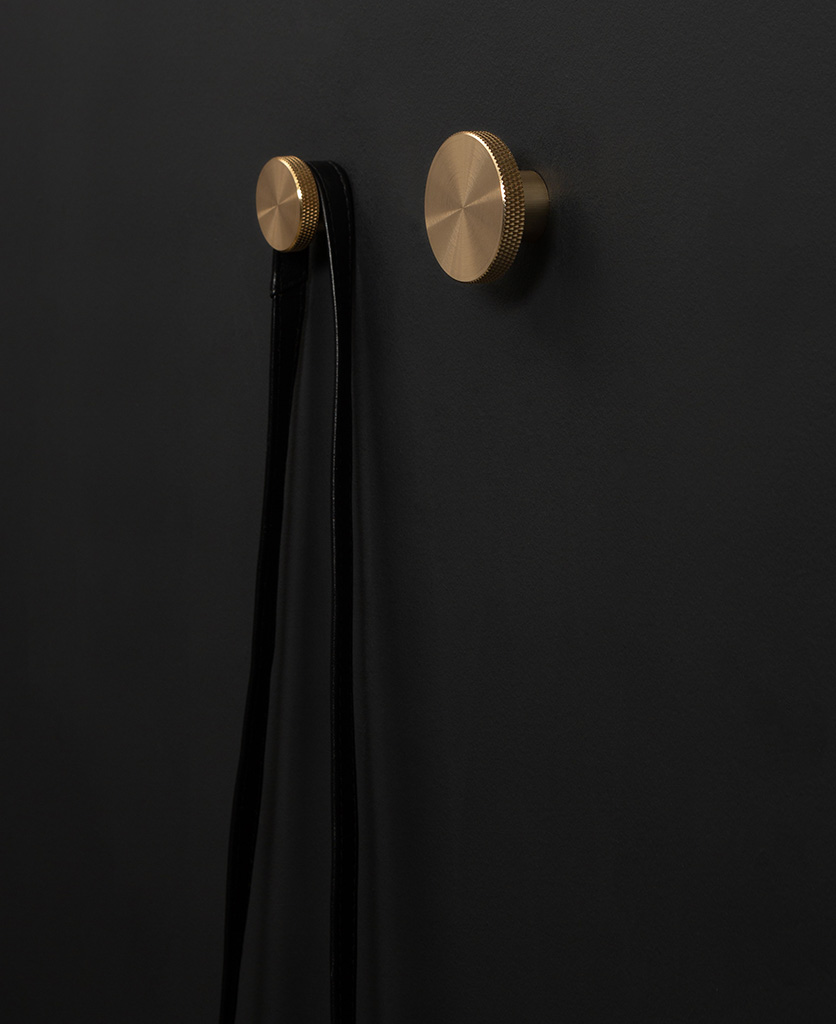 Modernist wall hook in gold attached to a black wall