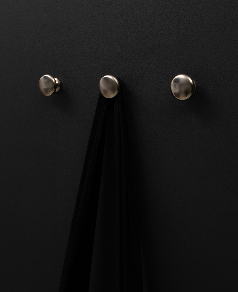 realist decorative wall hooks three silver wall hooks on a black wall face on