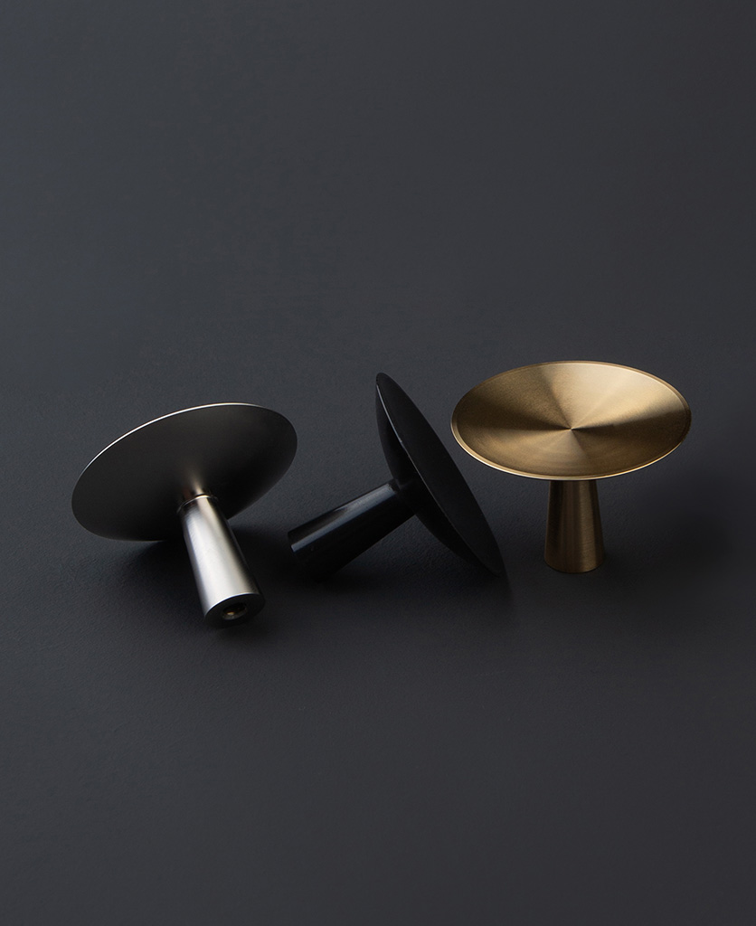 gold silver and black metal drawer handles and knobs against a black background