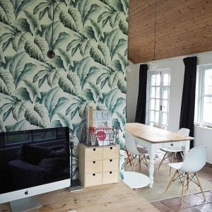 tropical print green wallpaper in an office space leading into white dining area with wooden cladded ceiling