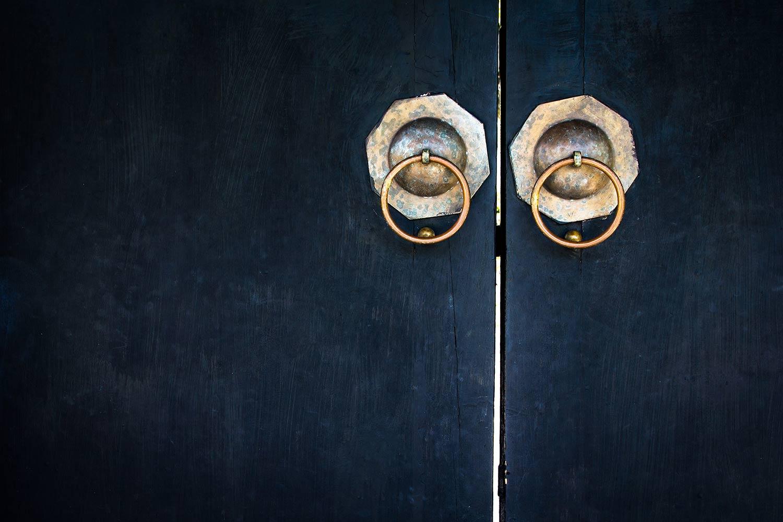 two brass door knockers on black wooden door