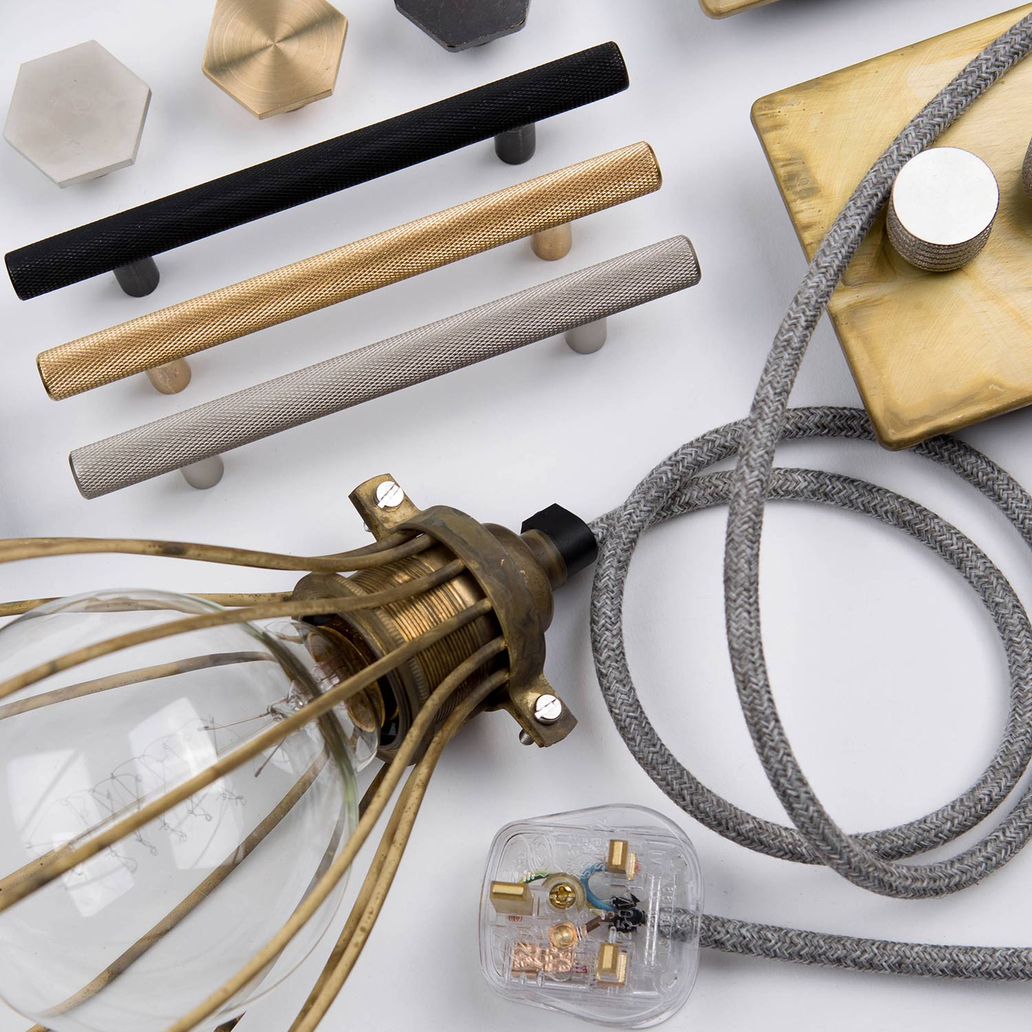 flatlay of skyscraper handles, smoked gold double dimmer, smoked gold balloon cage and bauhaus knobs against white background