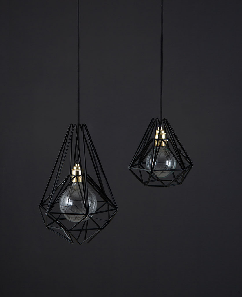 cage pendant light black two black metal diaamond shaped cage light shades with gold bulb holders suspended from black fabric cable against dark grey wall