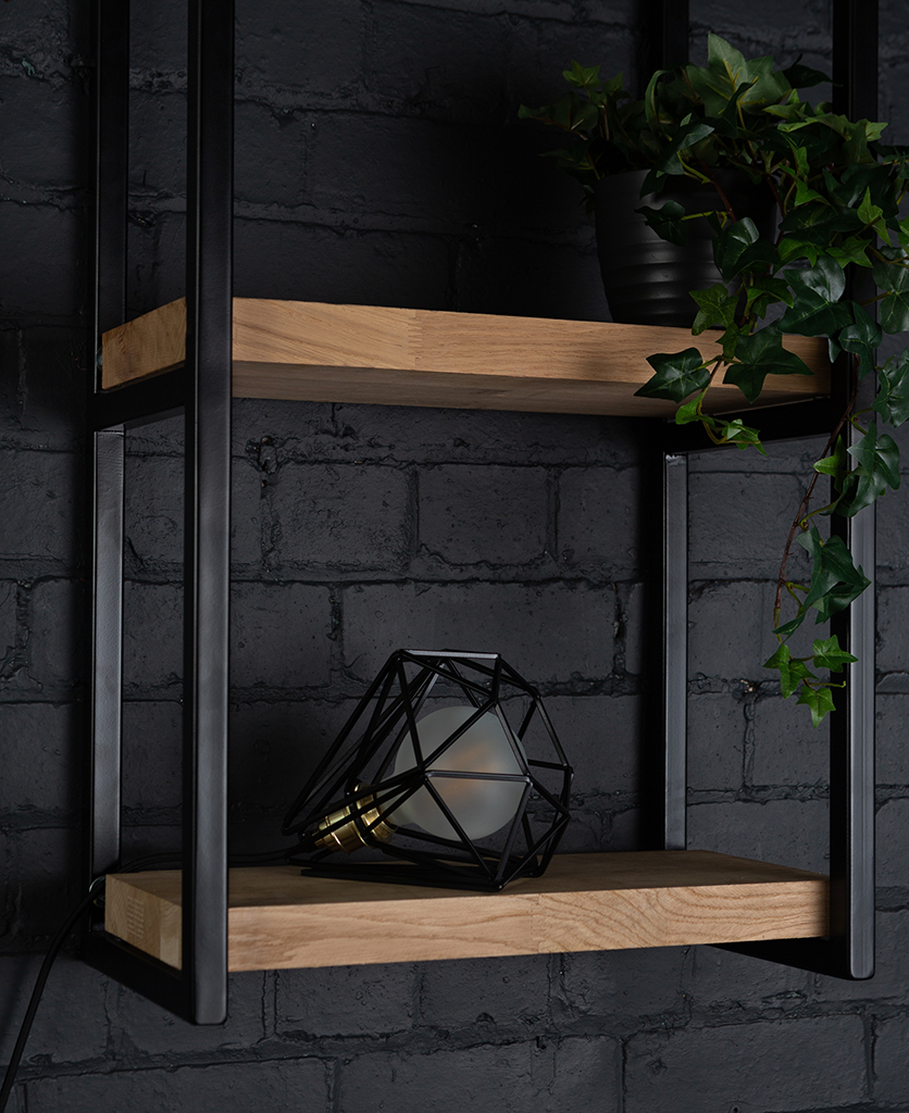 Black cage shade table lamp on wooden shelf with frosted bulb switched off