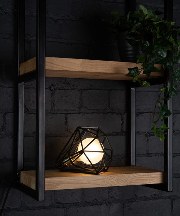 Black cage shade table lamp on wooden shelf with frosted bulb switched on