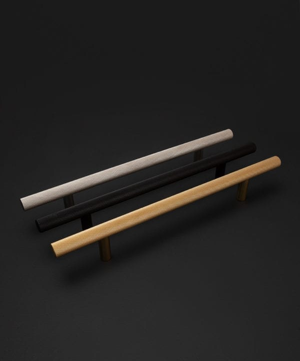 chunky skyscraper kitchen door handles in silver, black and brass against black background