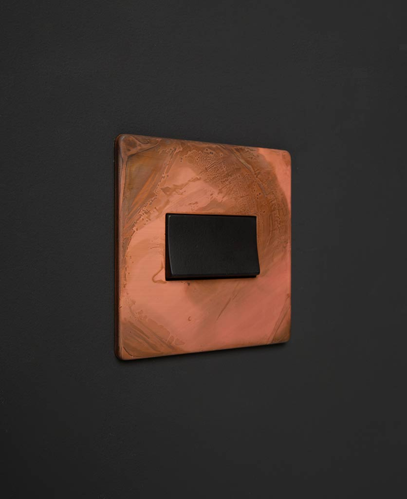 copper and black fan switch against black background