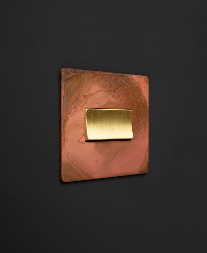 copper and gold fan switch against black background