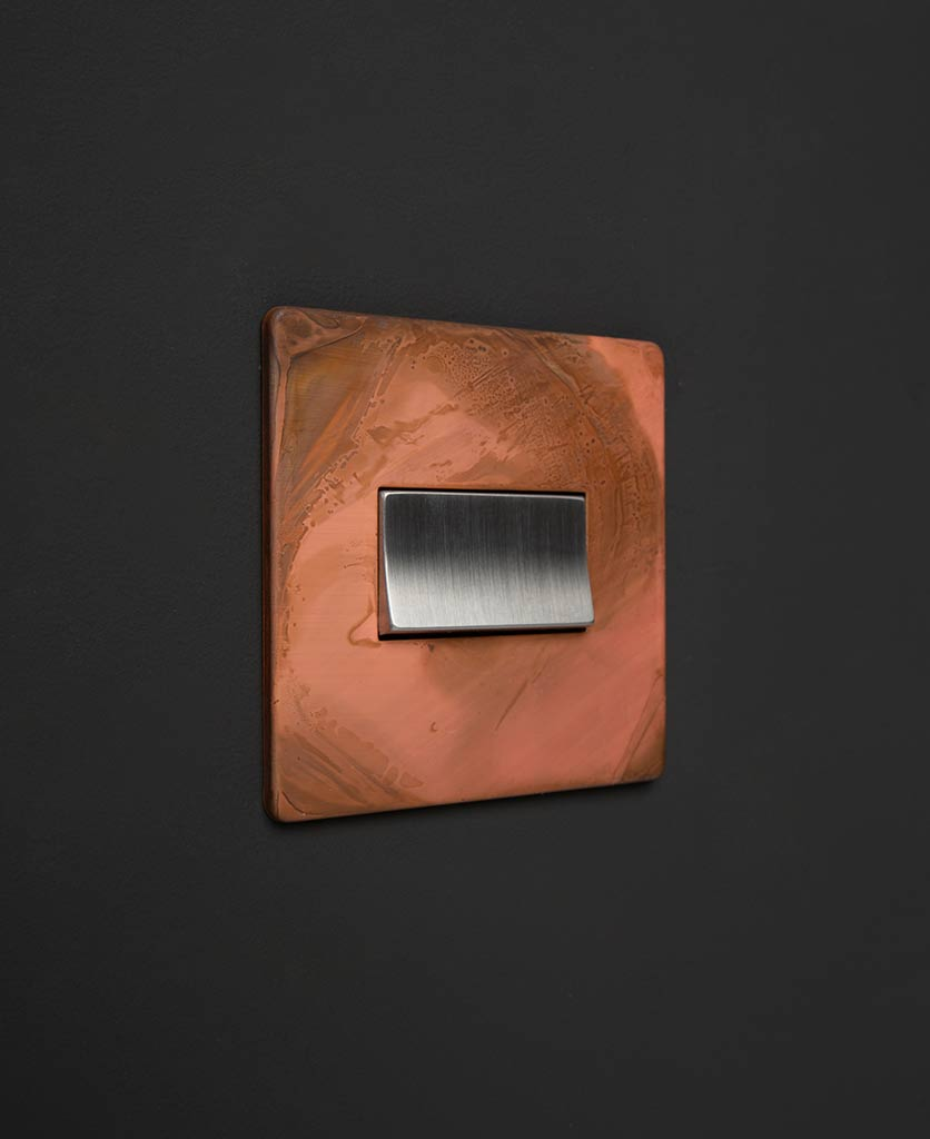 copper and silver fan switch against black background