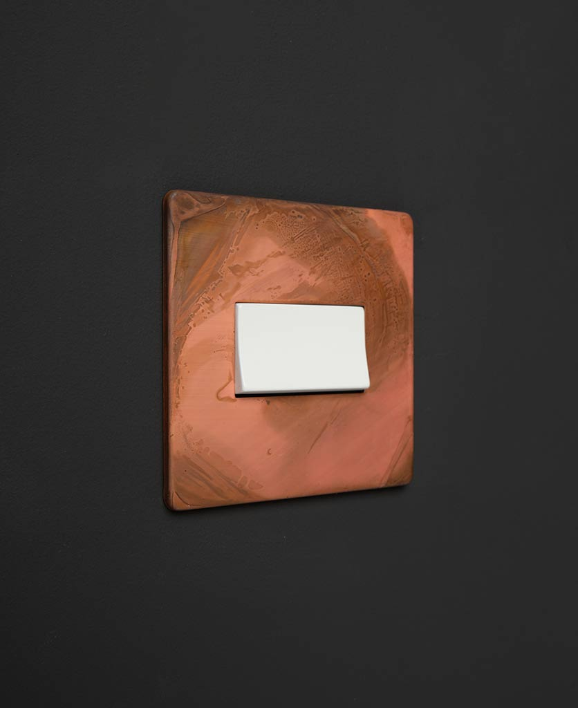 copper and white fan switch against black background