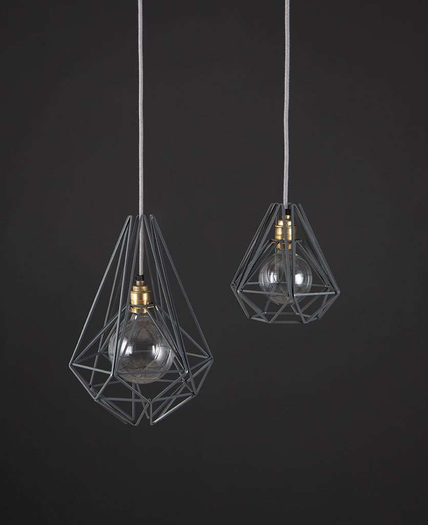 metal cage ceiling grey two black metal diaamond shaped cage light shades with smoked gold bulb holders suspended from felt grey fabric cable against dark grey wall