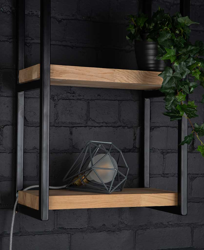 Grey cage shade table lamp on wooden shelf with frosted bulb switched off