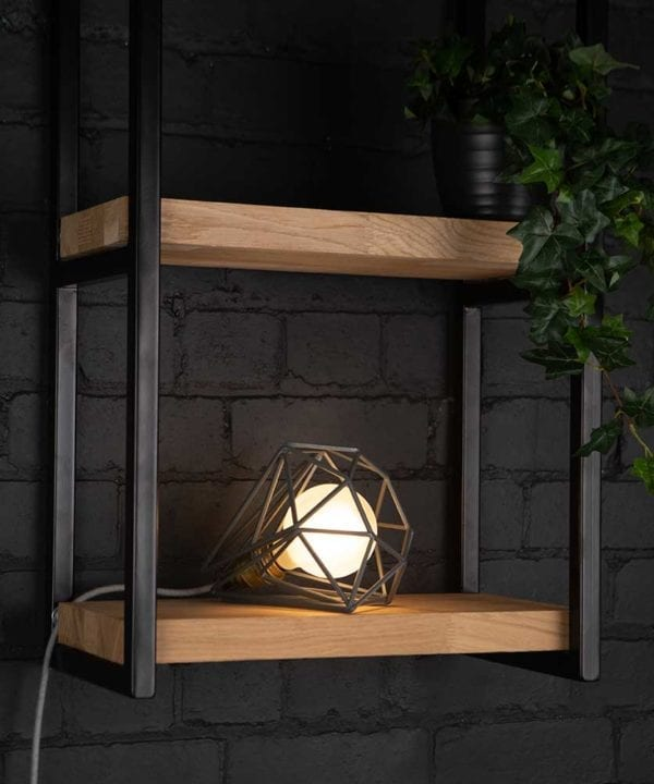 Grey cage shade table lamp on wooden shelf with frosted bulb switched on