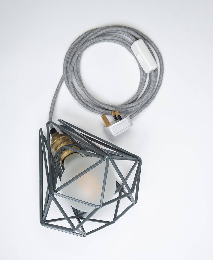Grey cage shade table lamp on white background with frosted bulb and grey cable switched off