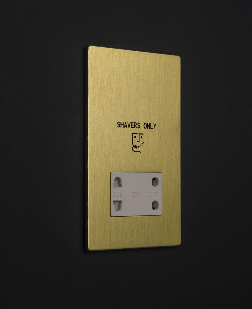 gold & white shaver socket against black background