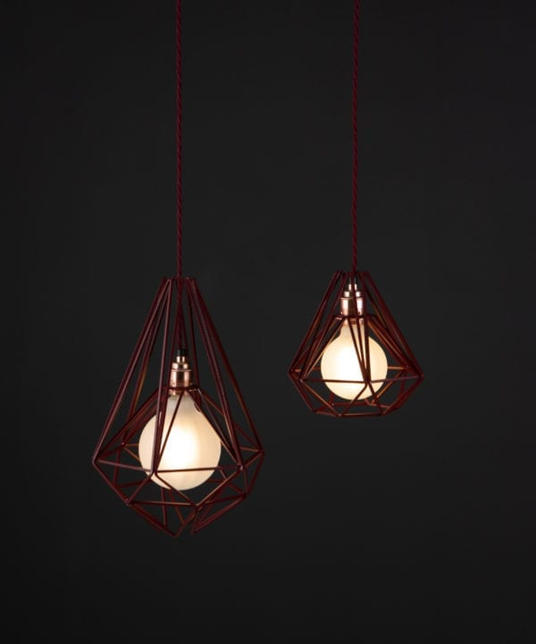 burgundy cage light with frosted bulbs suspended from burgundy twisted fabric cable against black background