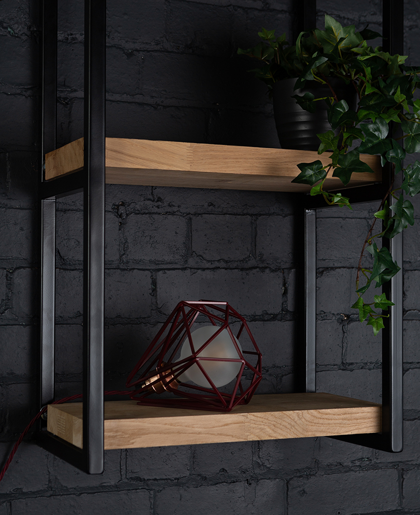 Burgundy cage shade table lamp on wooden shelf with frosted bulb switched off