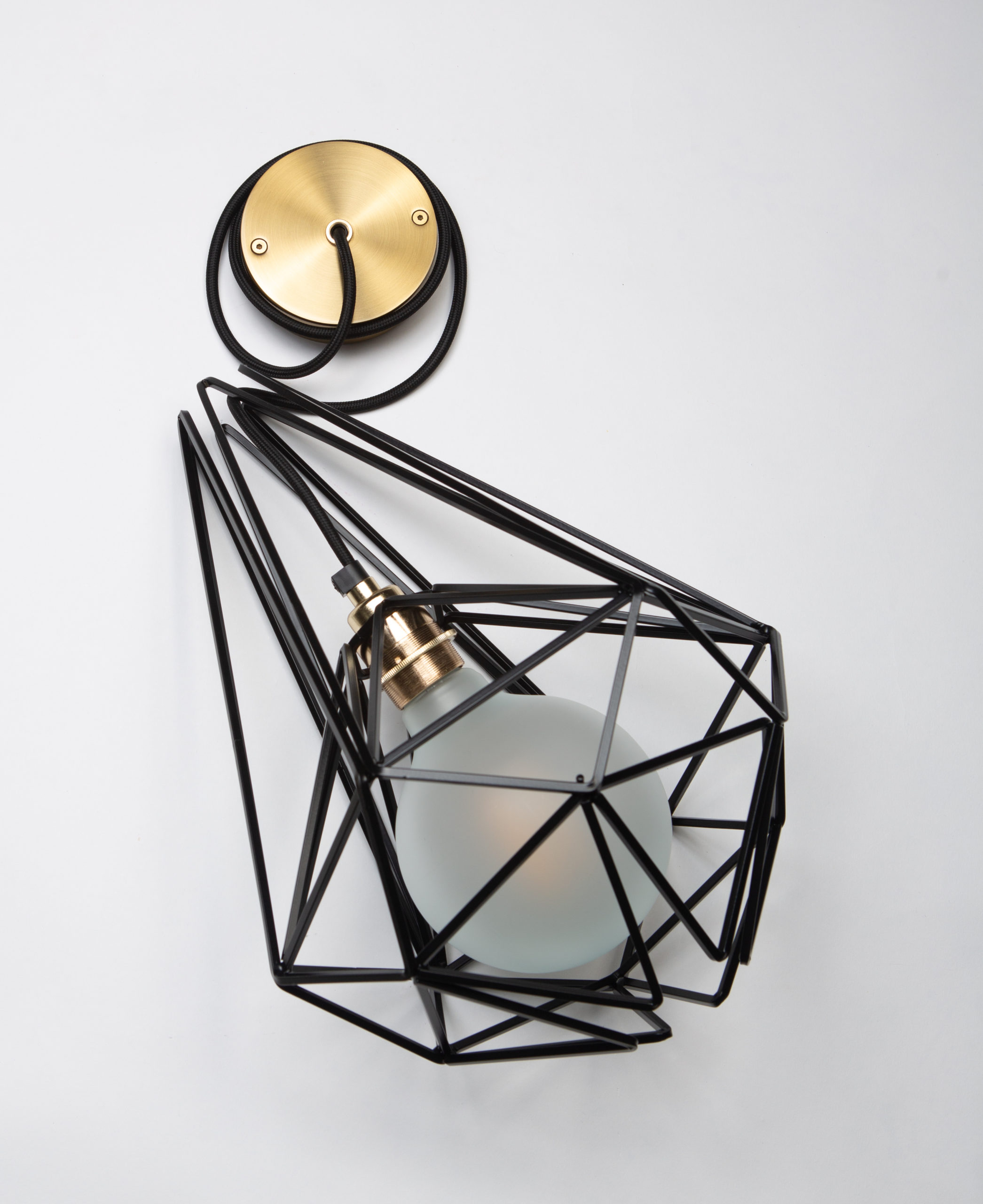large black cage pendant light with frosted light bulb, black fabric cable, gold bulb holder and gold ceiling rose against white background