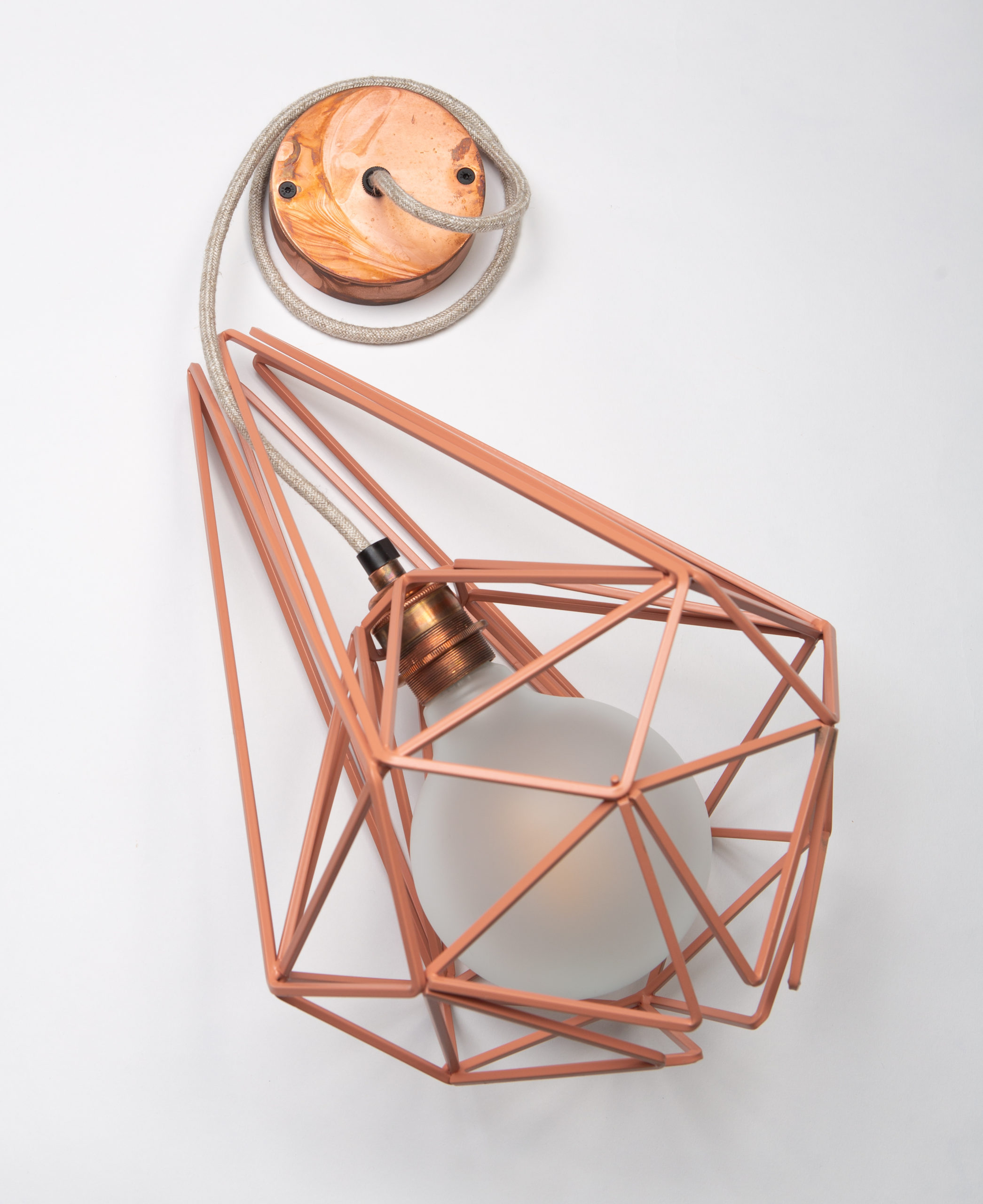 large pink metal cage pendant light with frosted bulb, linen fabric cable and tarnished copper bulb holder and ceiling rose against white background