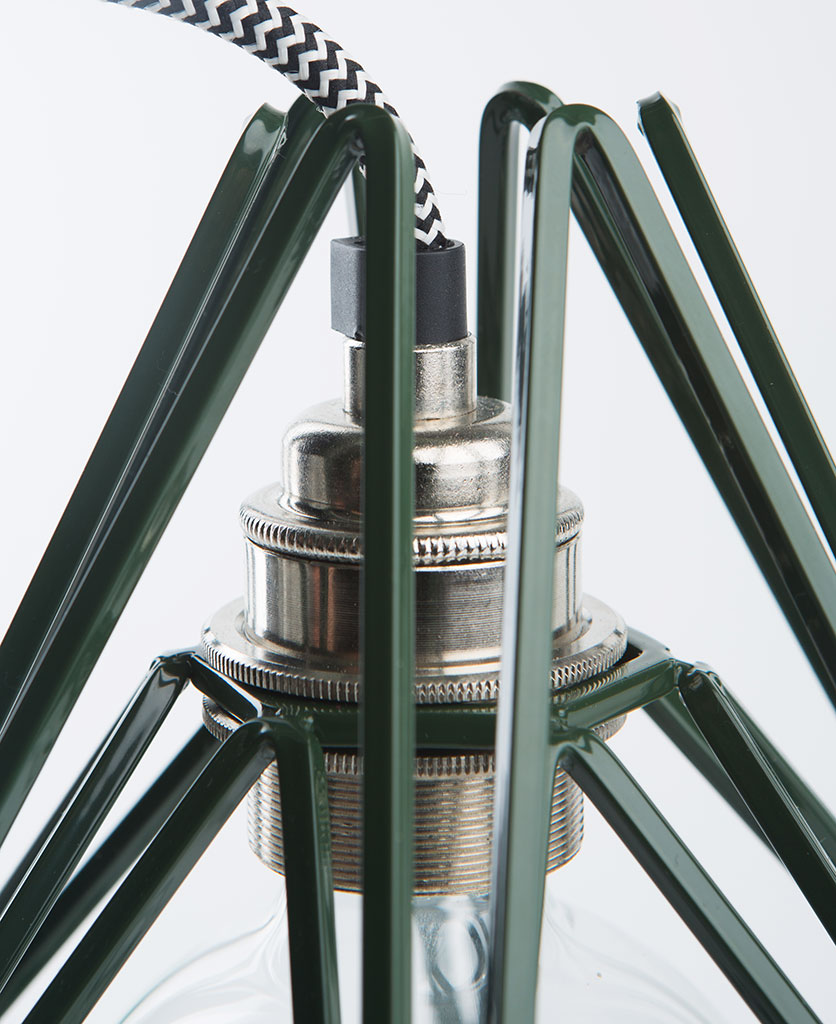 Closeup of green cage shade table lamp with silver bulb holder on white background