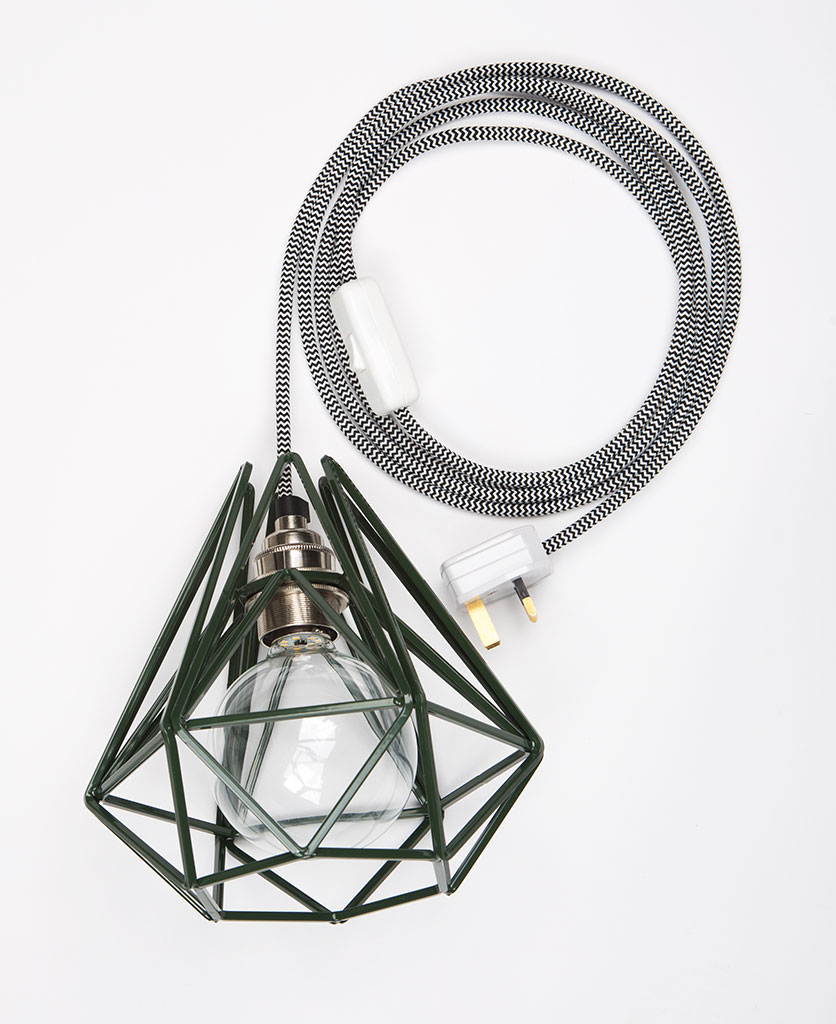 Green cage shade table lamp on white background with clear bulb, black and white cable, and silver bulb holder