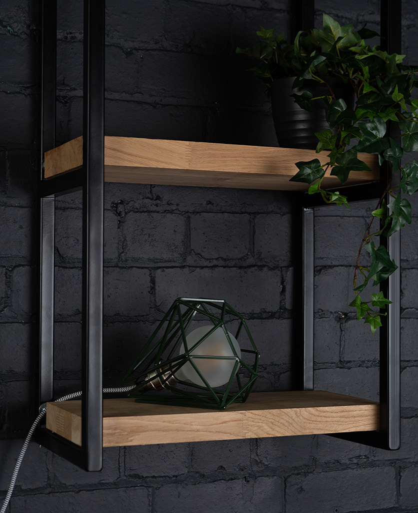 Green cage shade table lamp on wooden shelf with frosted bulb switched off