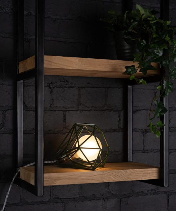 Green cage shade table lamp on wooden shelf with frosted bulb switched on