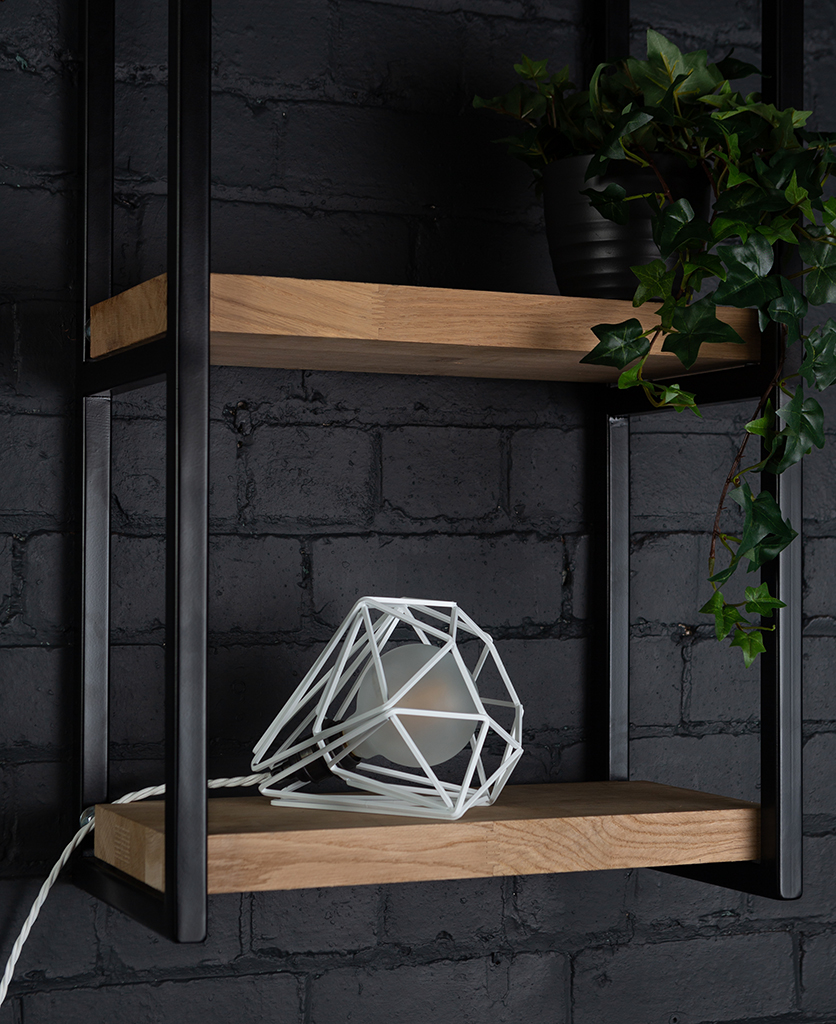 White cage shade table lamp on wooden shelf with frosted bulb switched off