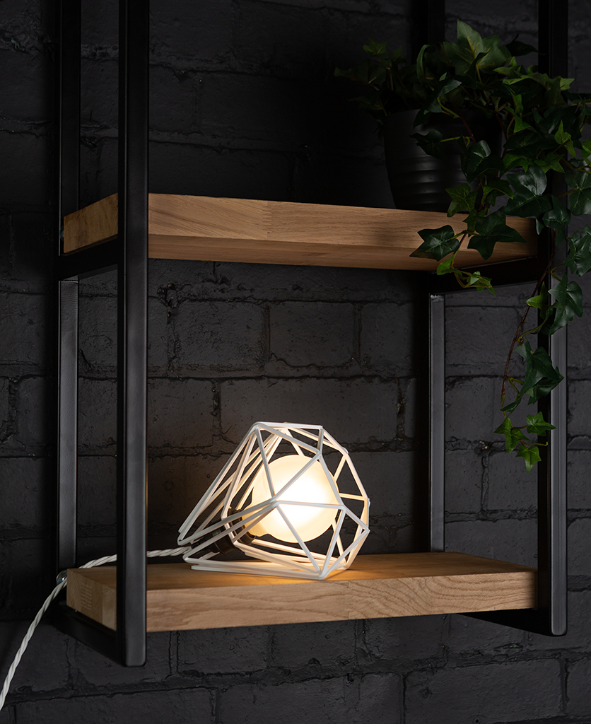 White cage shade table lamp on wooden shelf with frosted bulb switched on