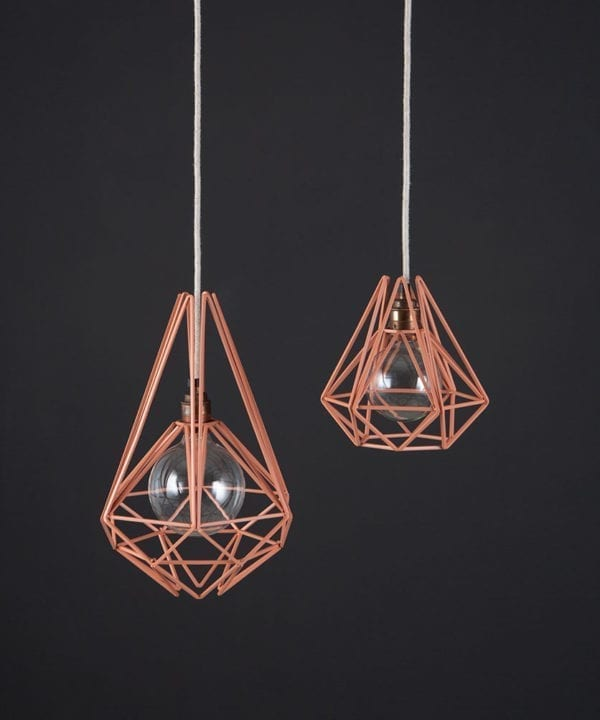 metal ceiling light pink chai two pink metal diamond shaped cage light shades with copper bulb holders suspended from linen fabric cable against dark grey wall