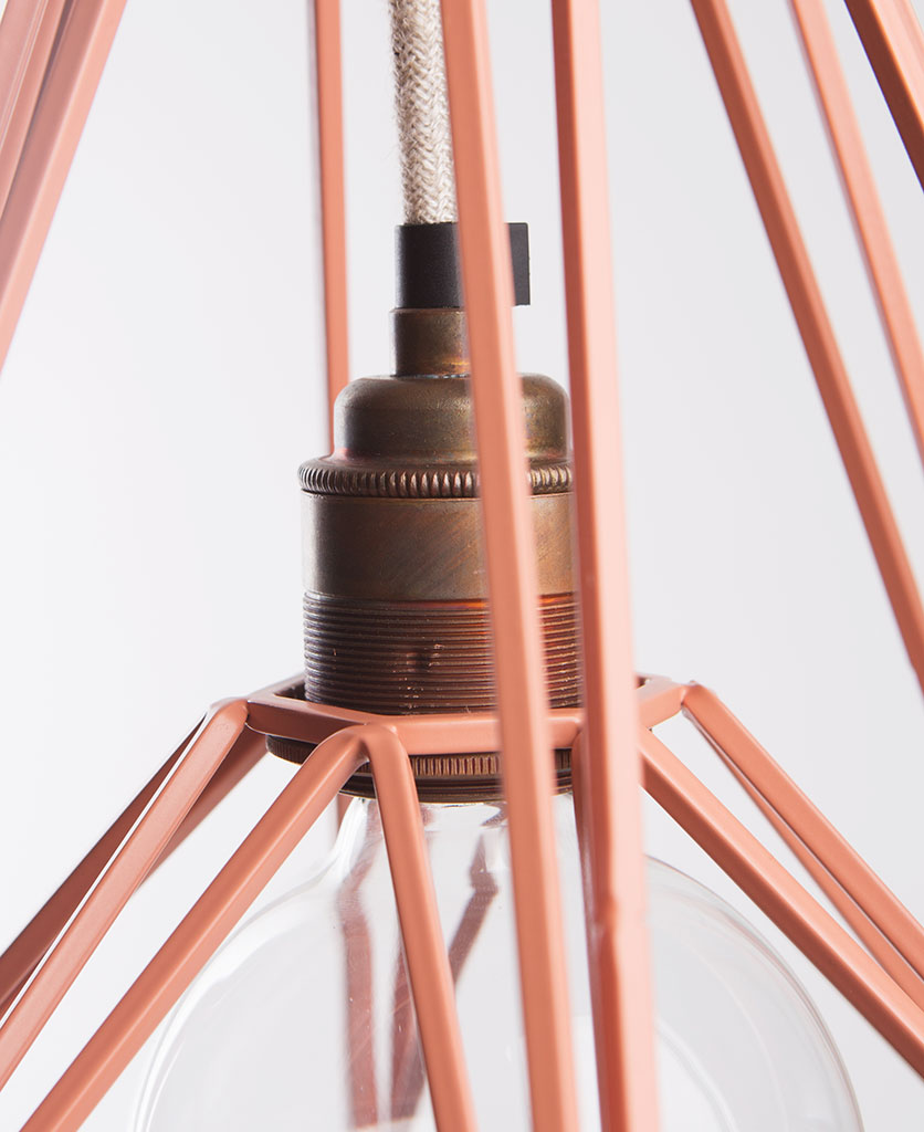 chai cage lamp shade closeup of pink light shade and copper bulb holder on white background
