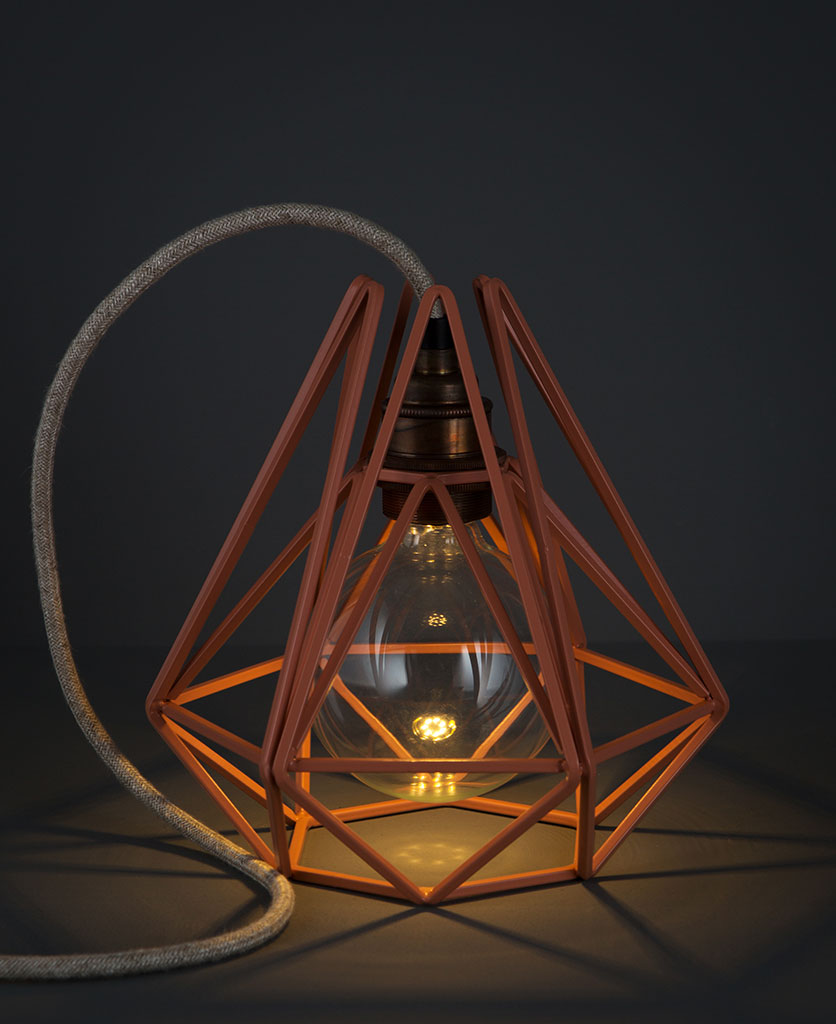 pink chai geometric light shade with lit bulb against black background